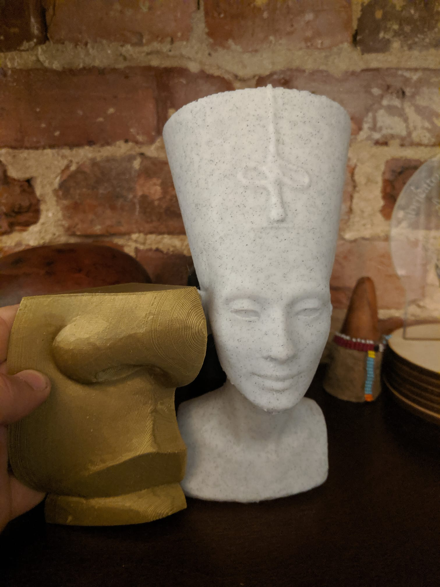a hand holds a 3d print in gold filament of a nose and lips, showing that it is larger than a smaller printed bust of Nefertiti