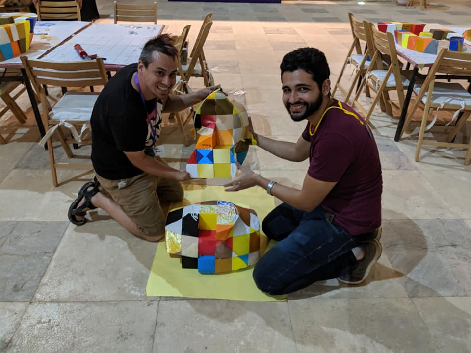 two assemblers smile at the camera holding one large assembled section above one on the ground, waiting with a layer of glue on top