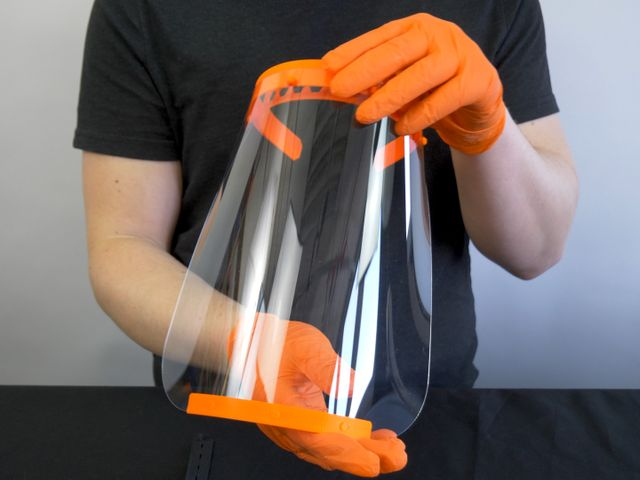 Hands in orange gloves holding a large clear face shield with stiff orange parts at the top and bottom